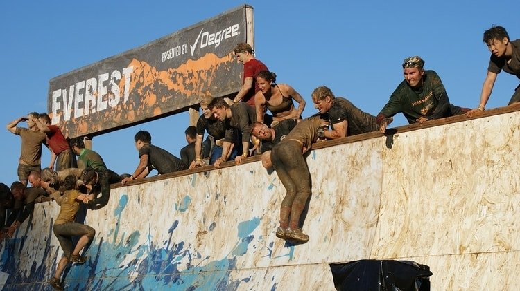 racers climbing over obstacle