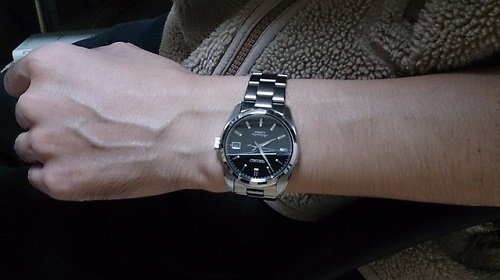 stainless steel watch on mans arm