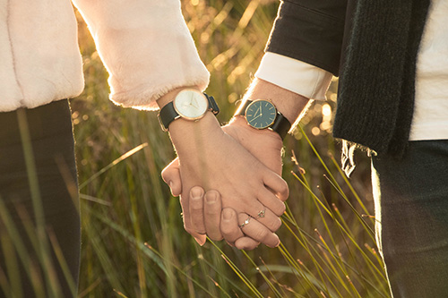 Two person holding hands wearing wristwatches