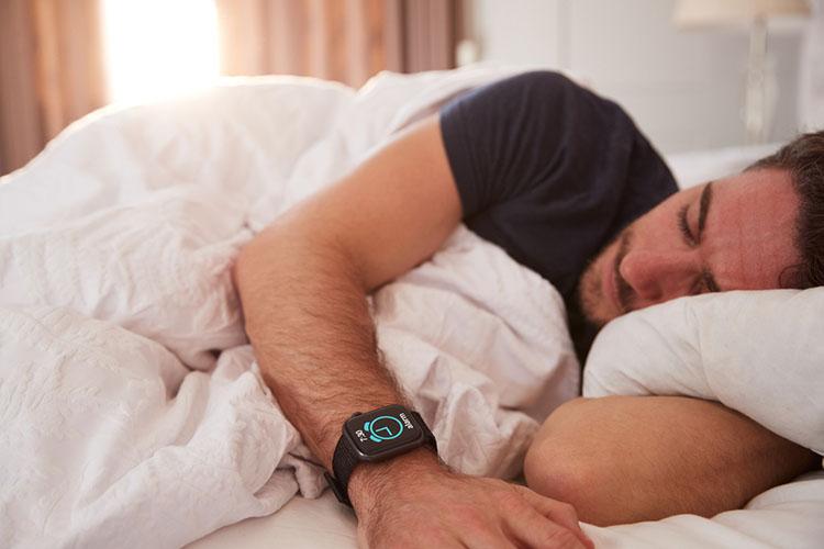 Man Asleep In Bed Wearing Smart Watch