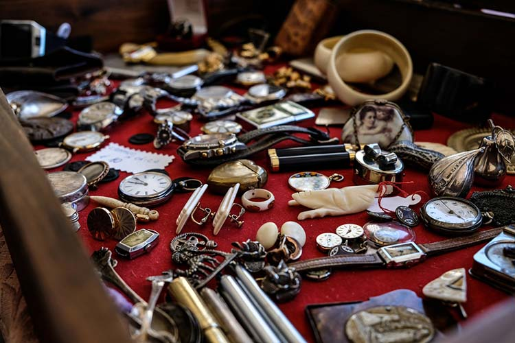 Closeup of different vintage watches and jewelry on a red surfa